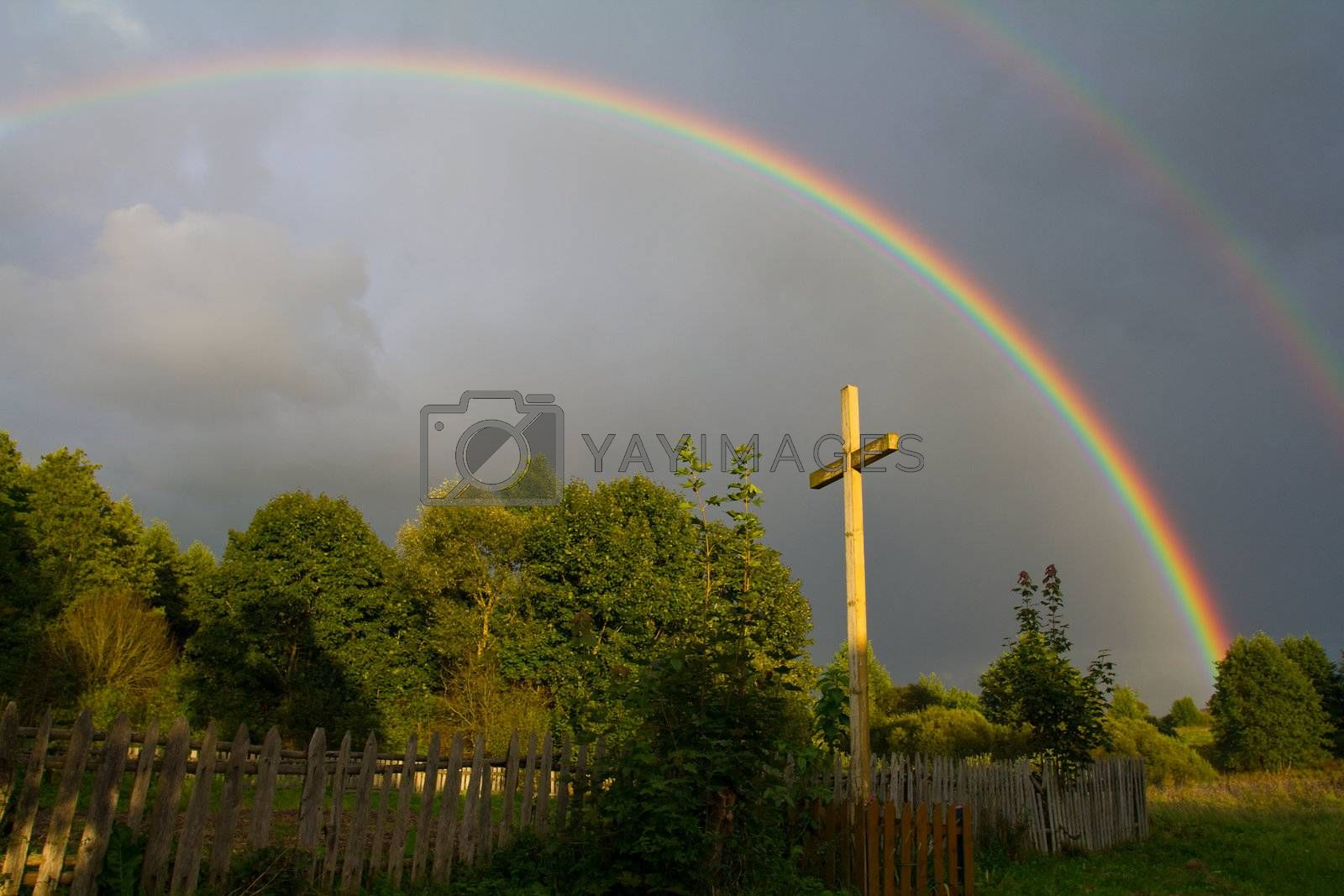 cross and rainbow after summer rain