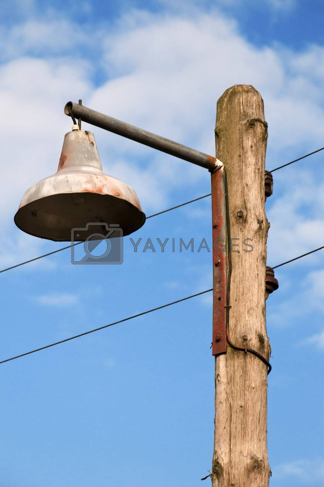 Old Lantern on a Wooden Pole Against a Blue Sky