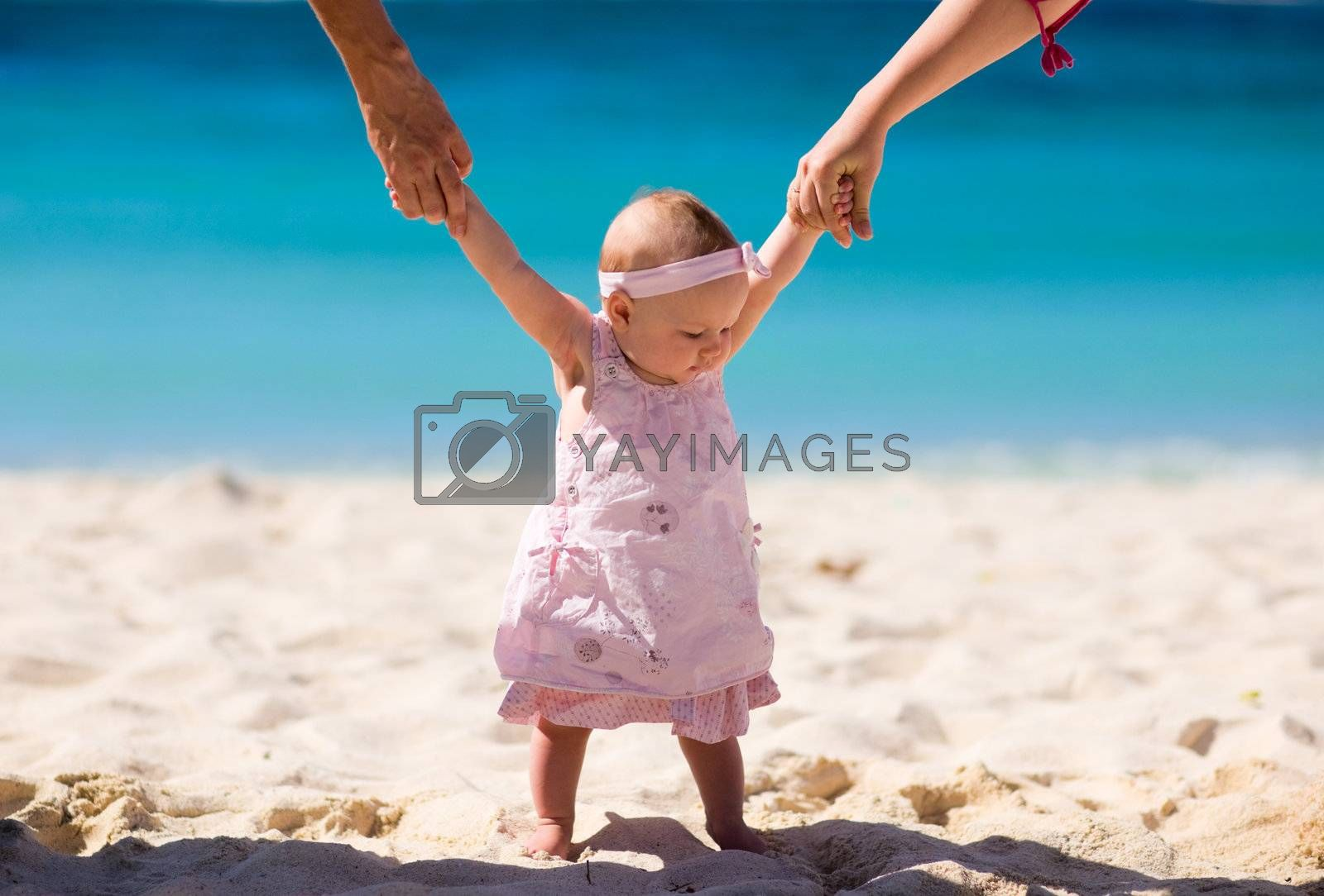 4 months baby girl on white sand tropical beach.