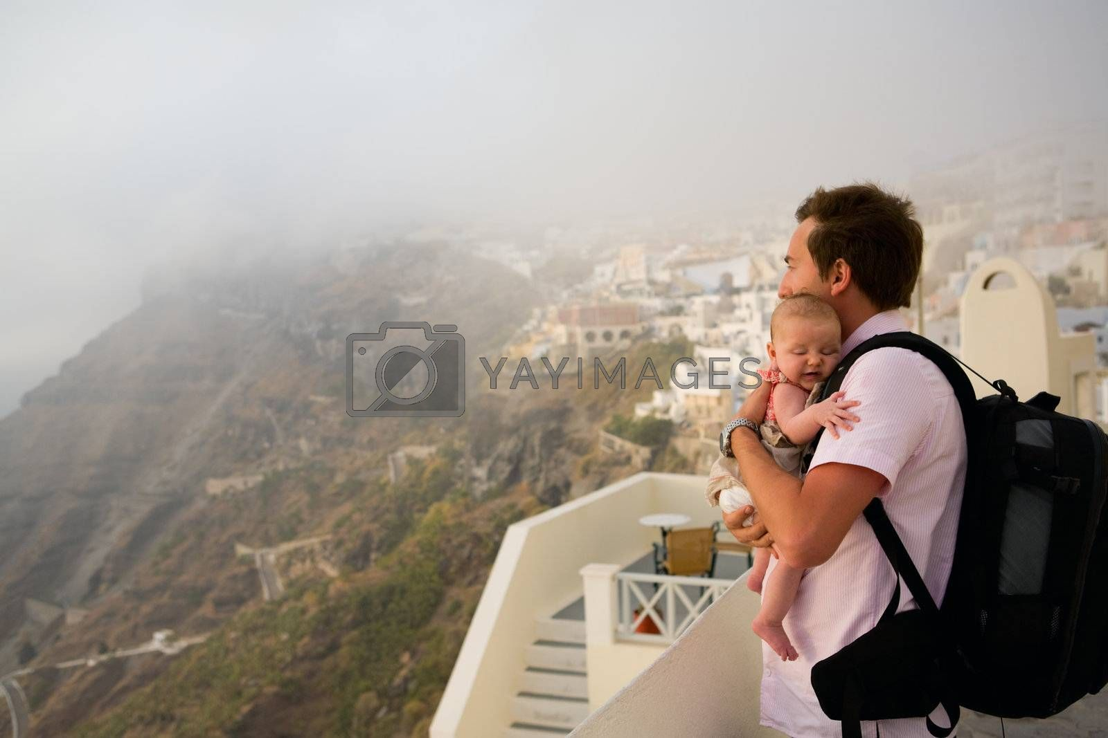 Father and his baby daughter enjoying views of town in fog