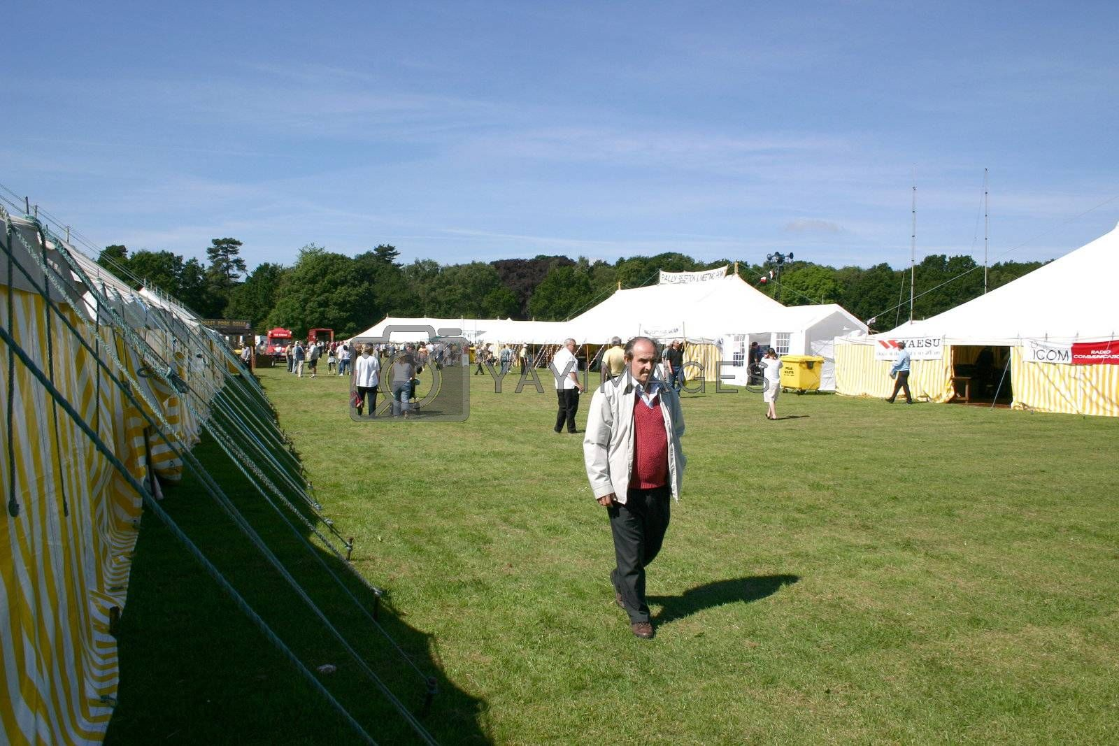 man walking around a showground in between the tents