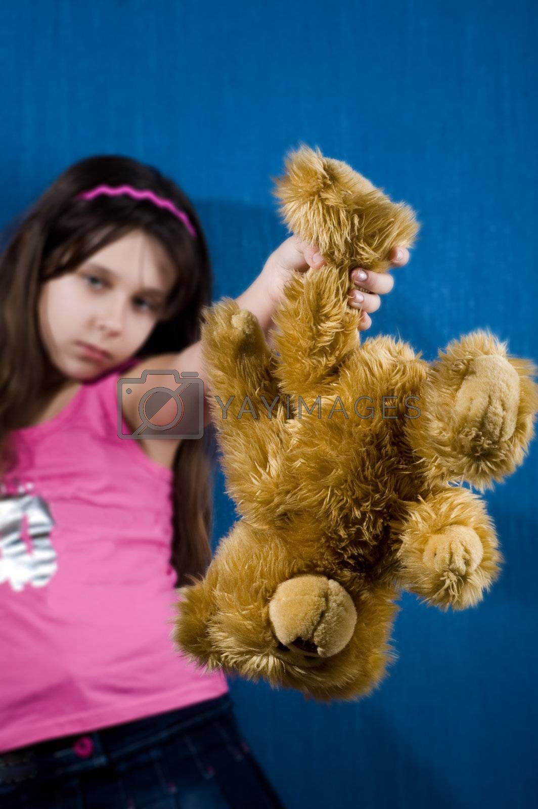 Royalty free image of Angry girl holding teddybear by iribo