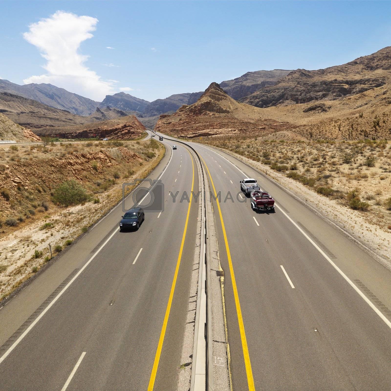 Birds eye view of automobiles on rural desert highway.