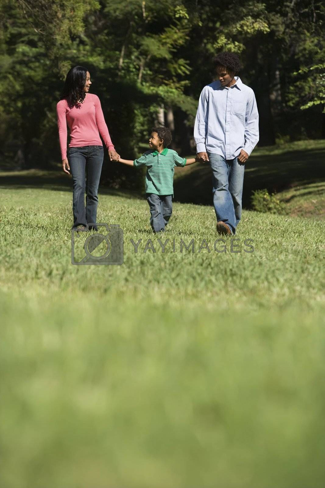 Parents and young son walking in park holding hands.