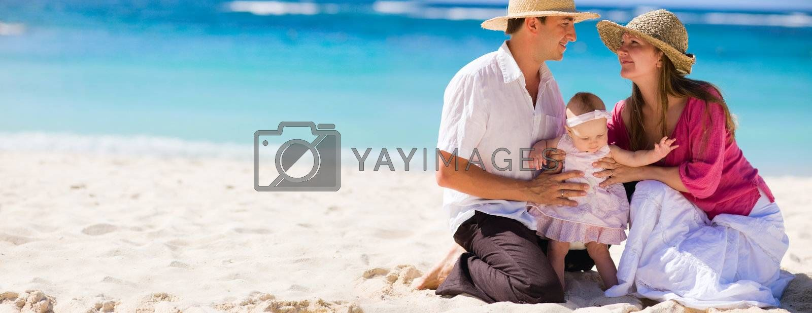 Family vacation. Panoramic photo of young family of three on white sand tropical beach