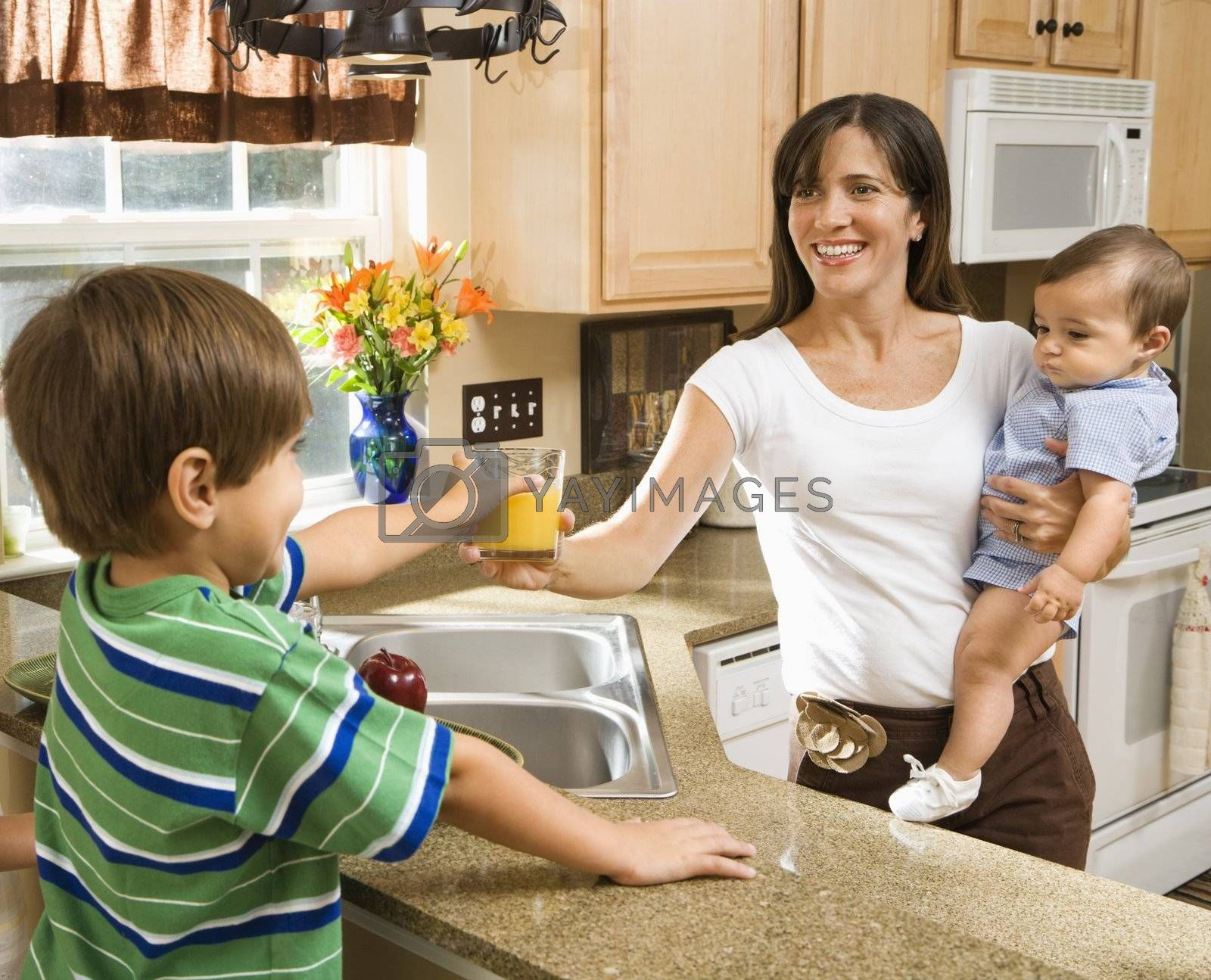 Hispanic mother and children in kitchen with juice.