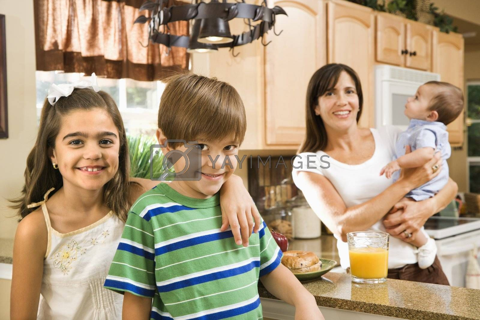 Hispanic mother and children smiling at viewer in kitchen.