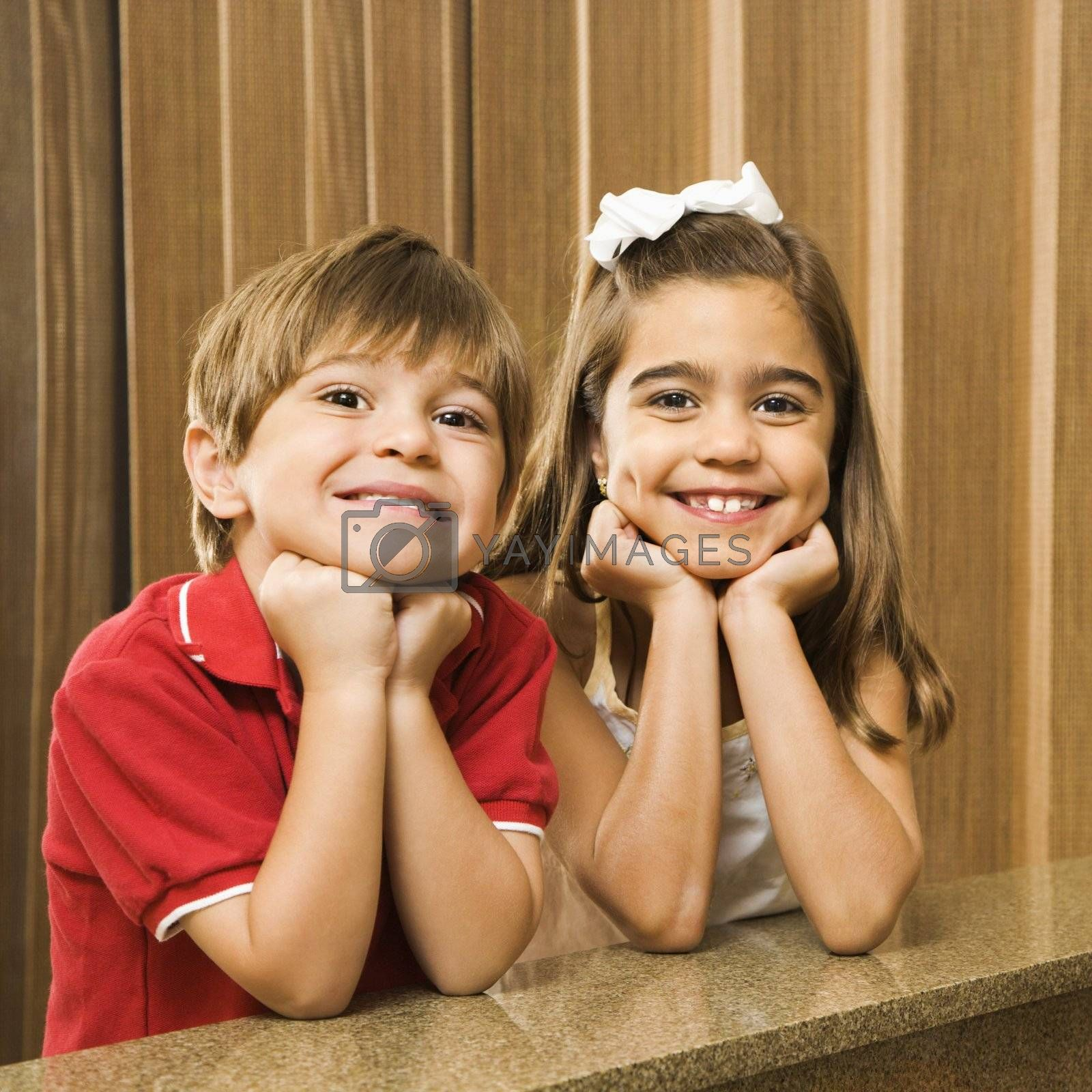 Hispanic children with their head on hands smiling at viewer.