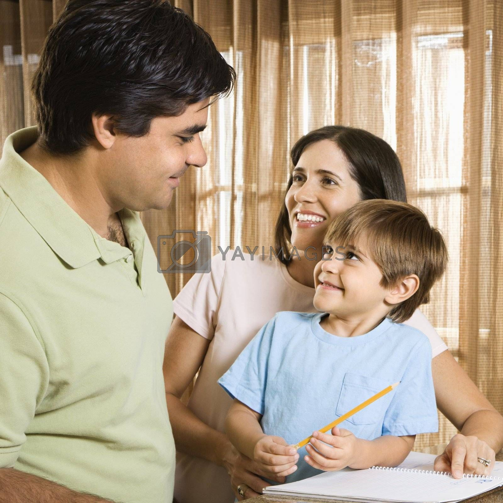 Hispanic parents making eye contact with son doing homework.
