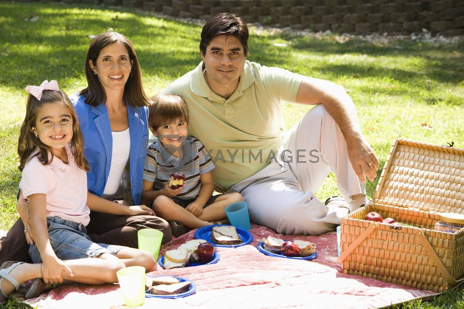 Hispanic family picnicking in the park and smiling at viewer.