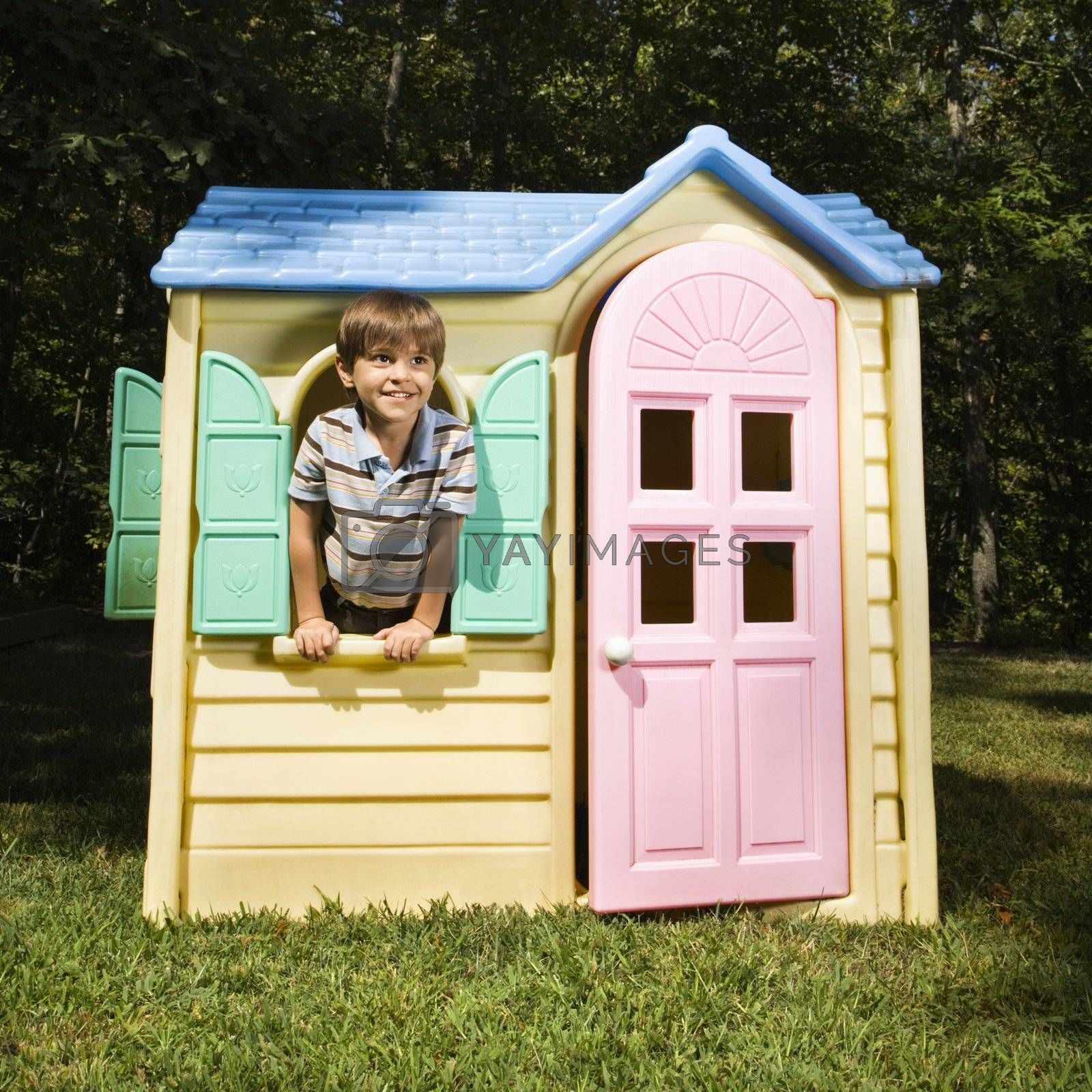 Hispanic boy in window of outdoor playhouse smiling at viewer.