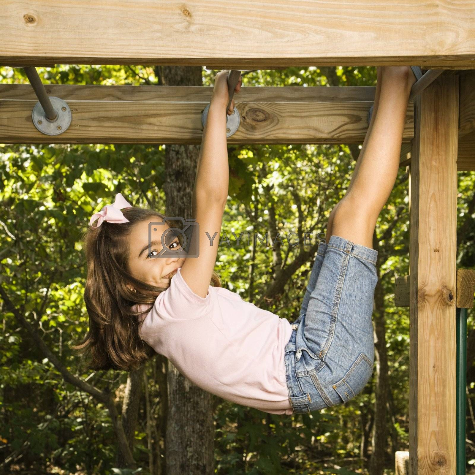 Side view of Hispanic girl hanging by arms and legs from monkey bars smiling at viewer.