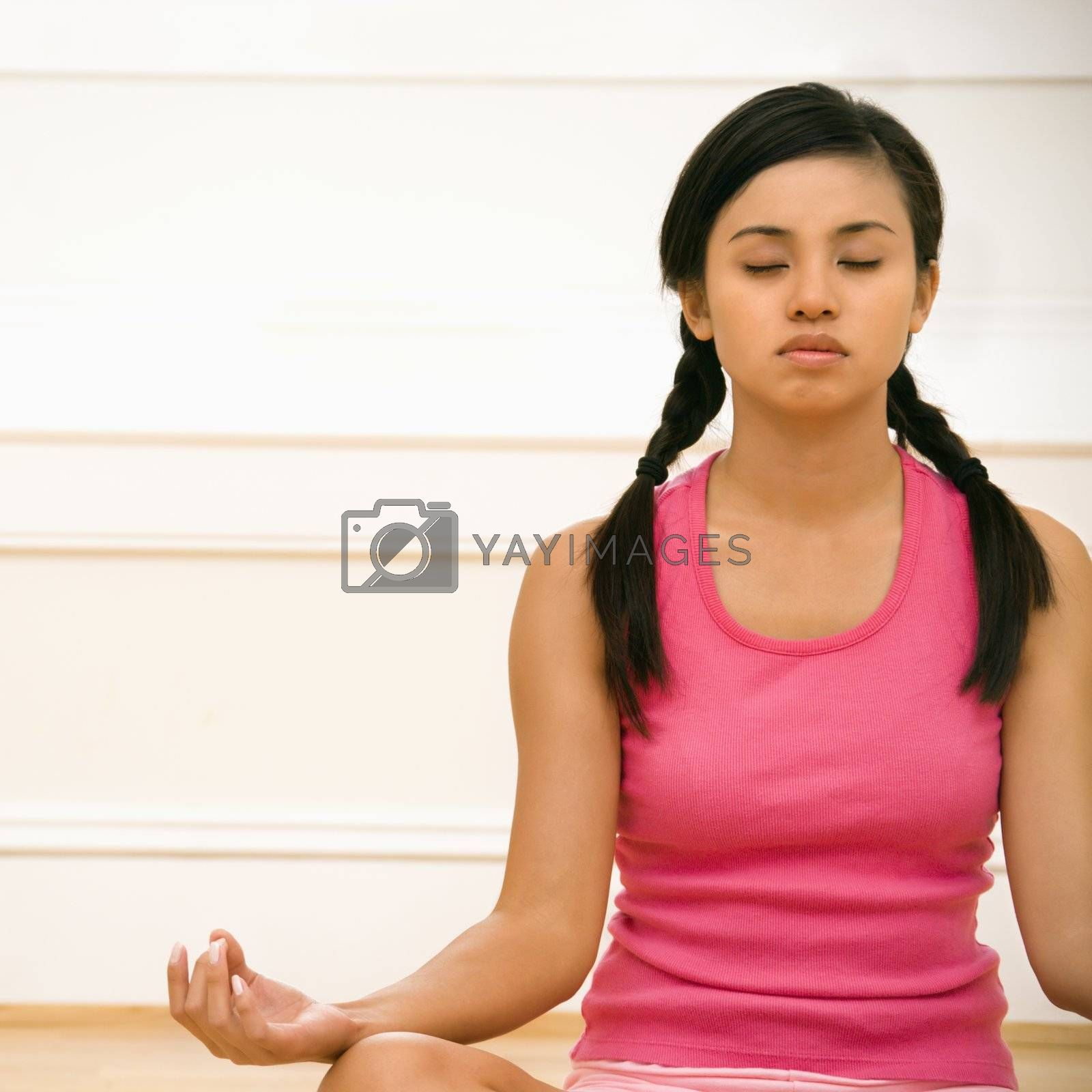Young woman sitting on floor meditating in yoga lotus pose with legs crossed and eyes closed.