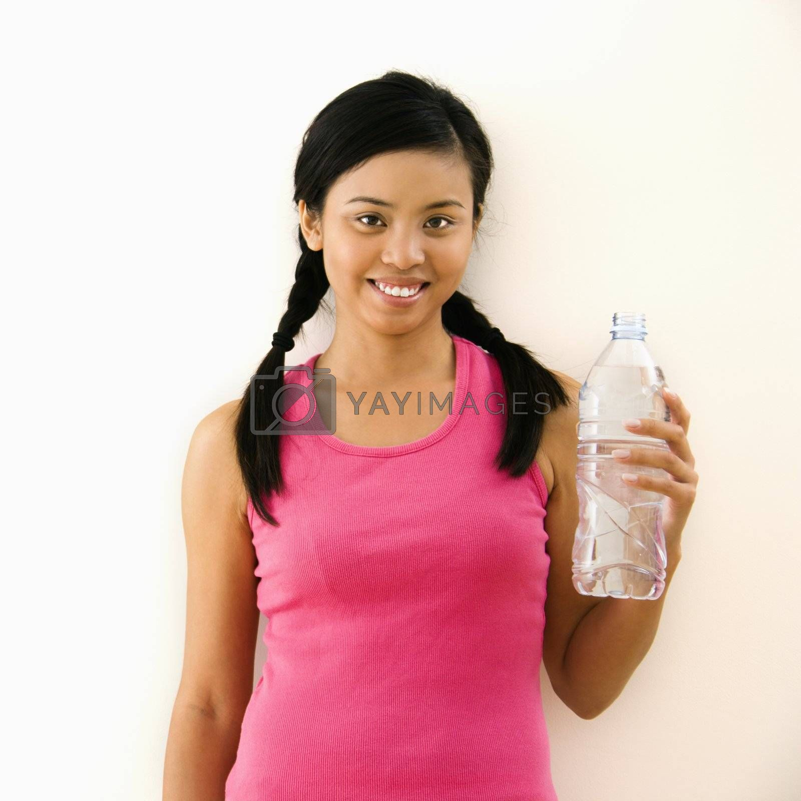 Young woman in fitness outfit holding bottled water and smiling.