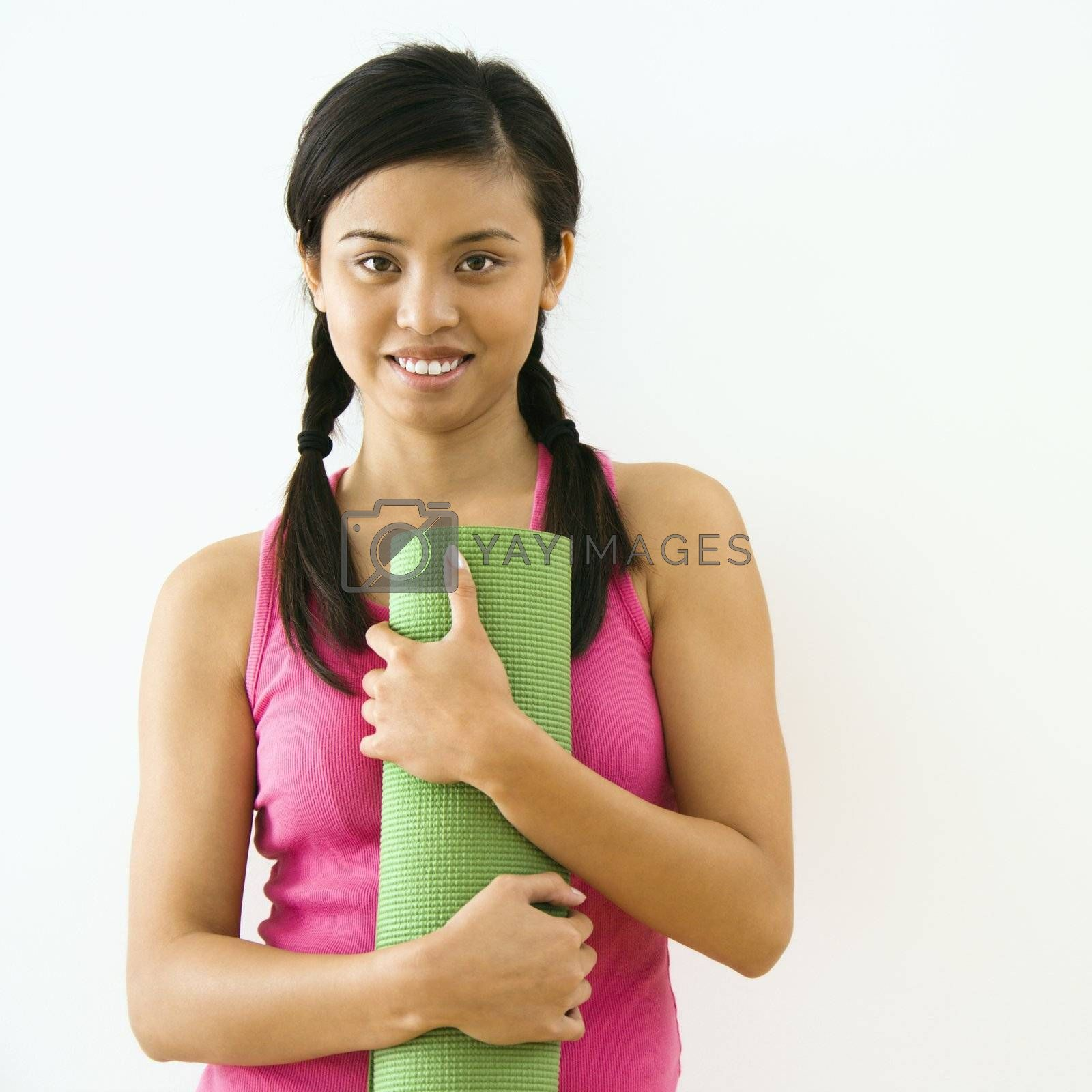 Portrait of smiling young Asian woman holding exercise mat.