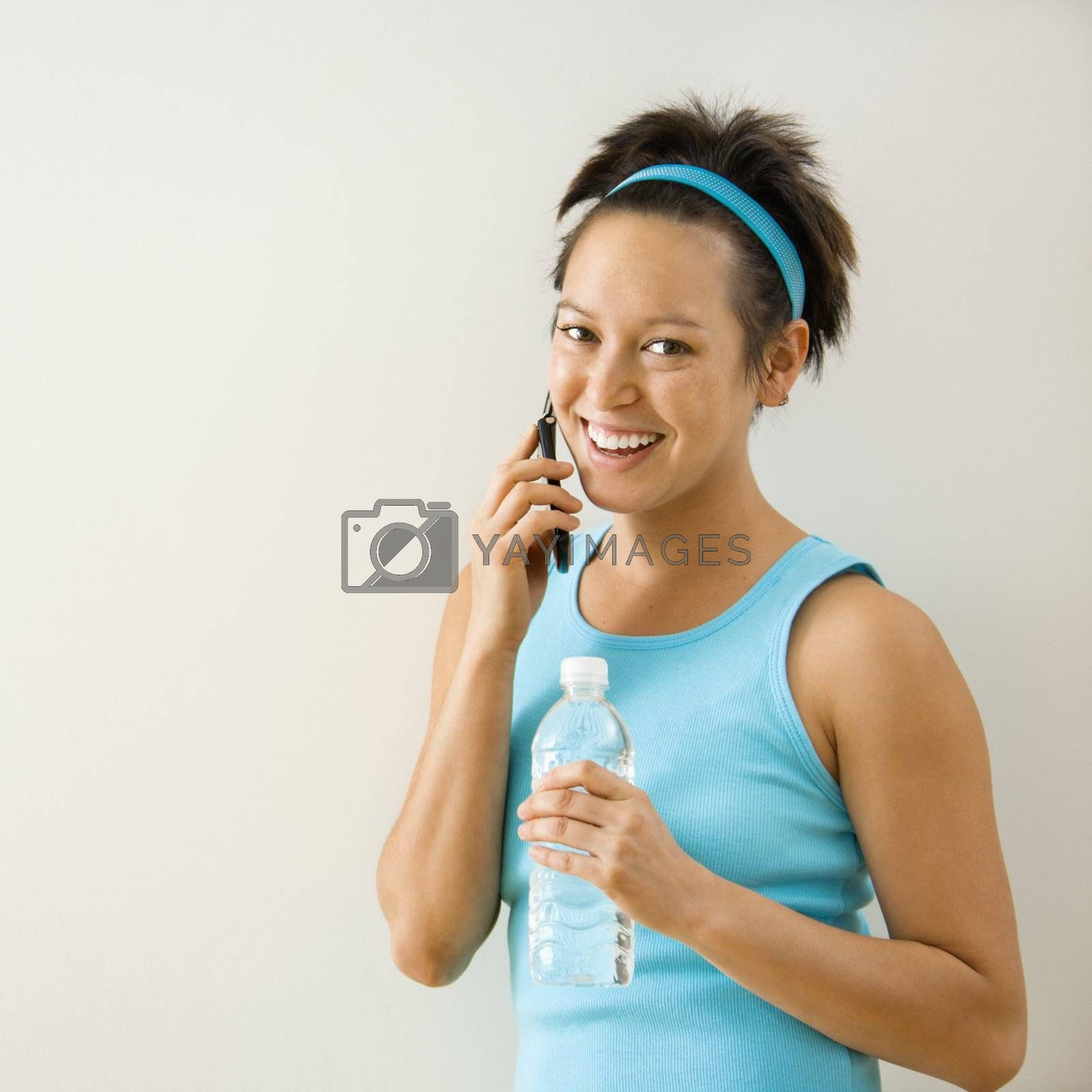 Young woman in fitness clothing holding bottled water talking on cellphone smiling.