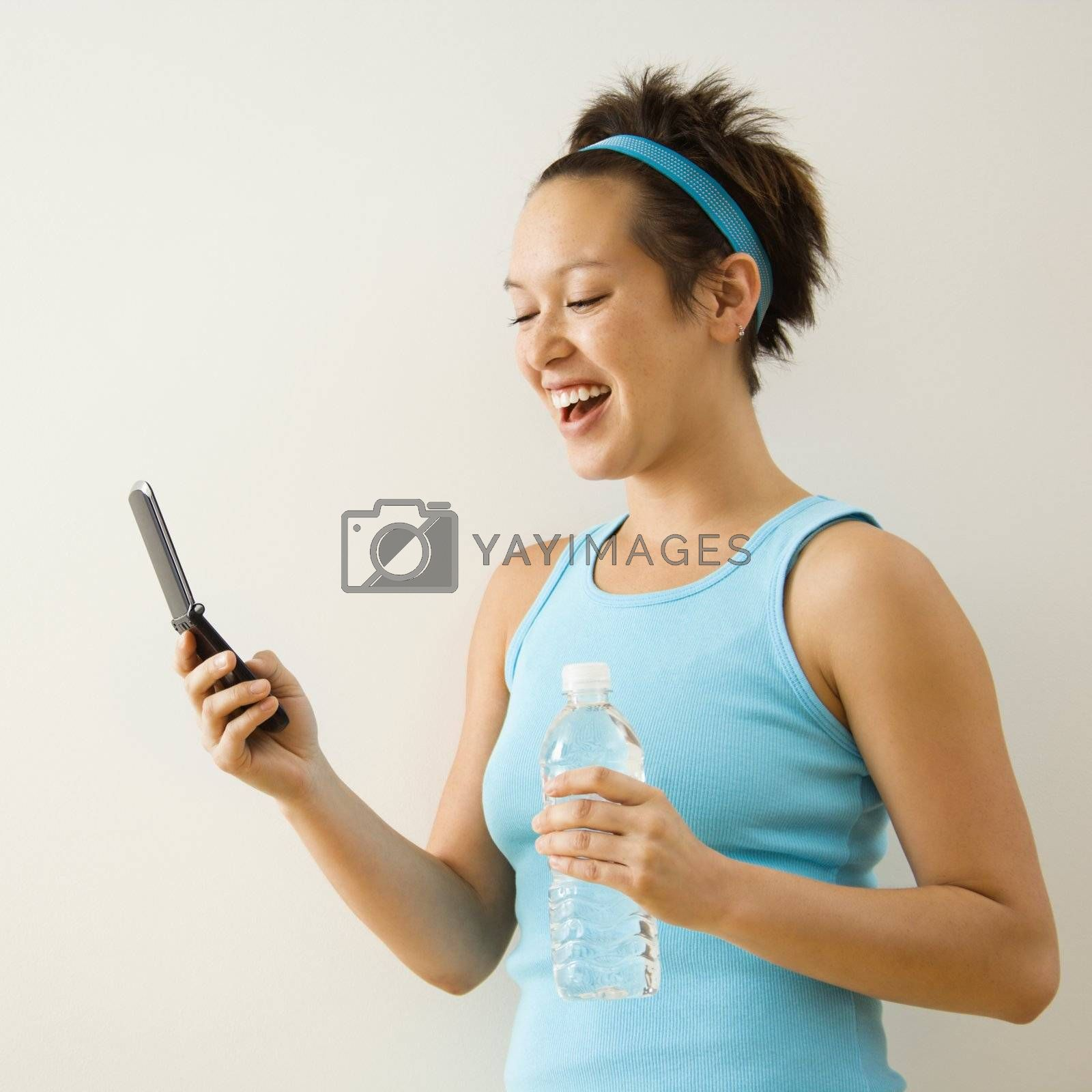 Young woman in fitness clothing holding bottled water and smiling at cellphone.
