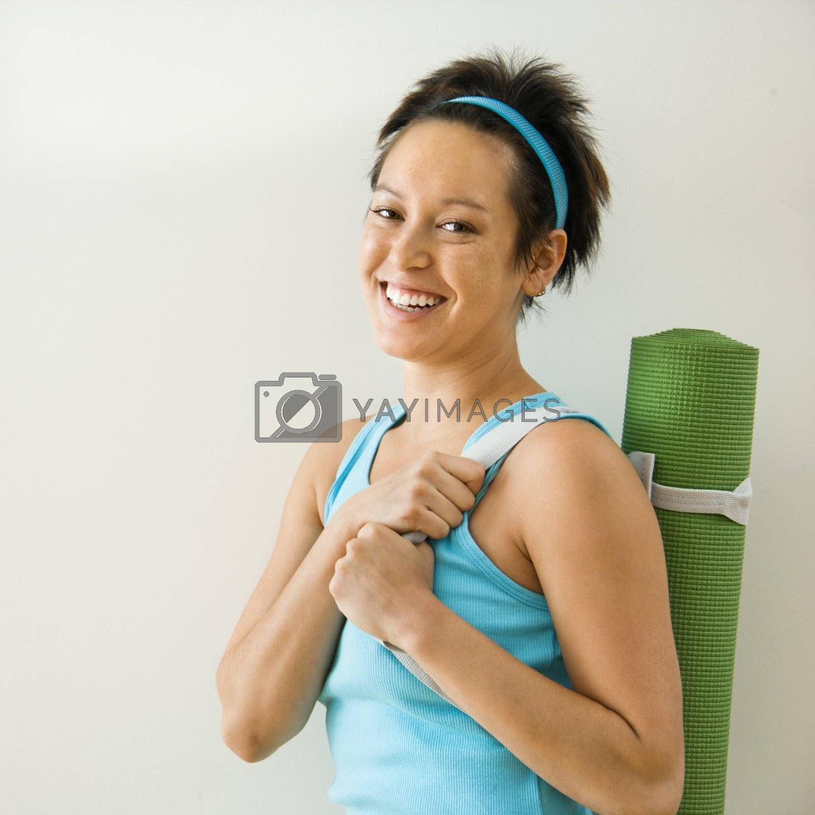 Young woman holding yoga mat and smiling.