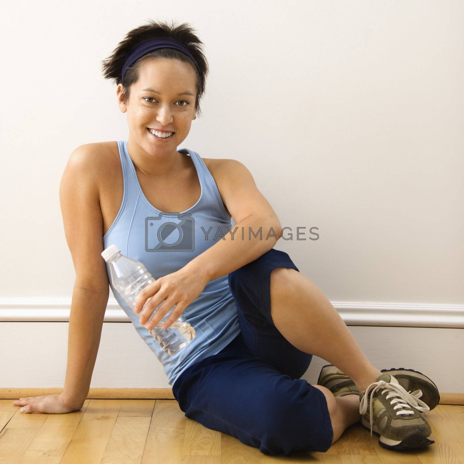 Young woman in fitness outfit sitting on floor with bottled water smiling.
