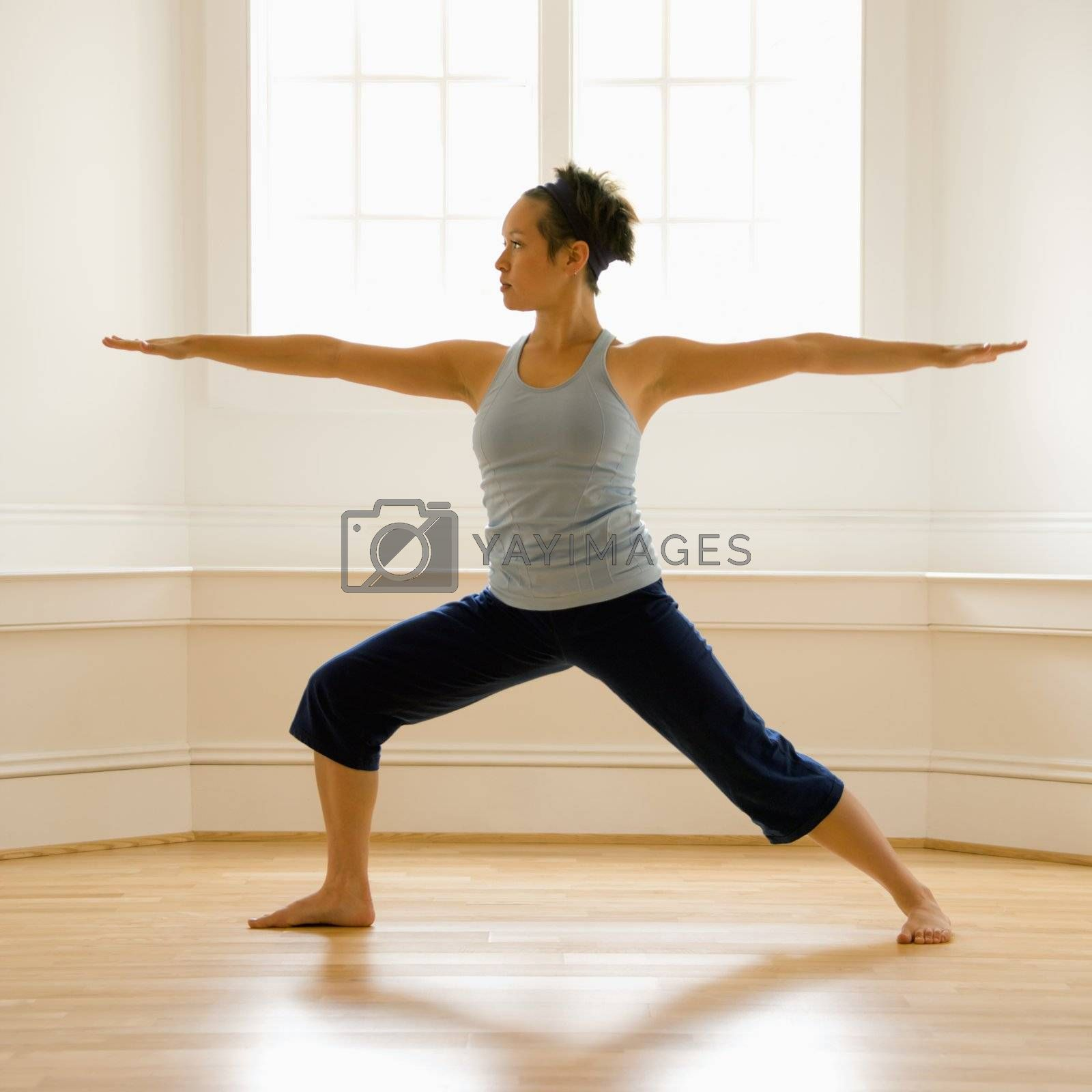 Young woman doing yoga warrior pose indoors by sunlit window.