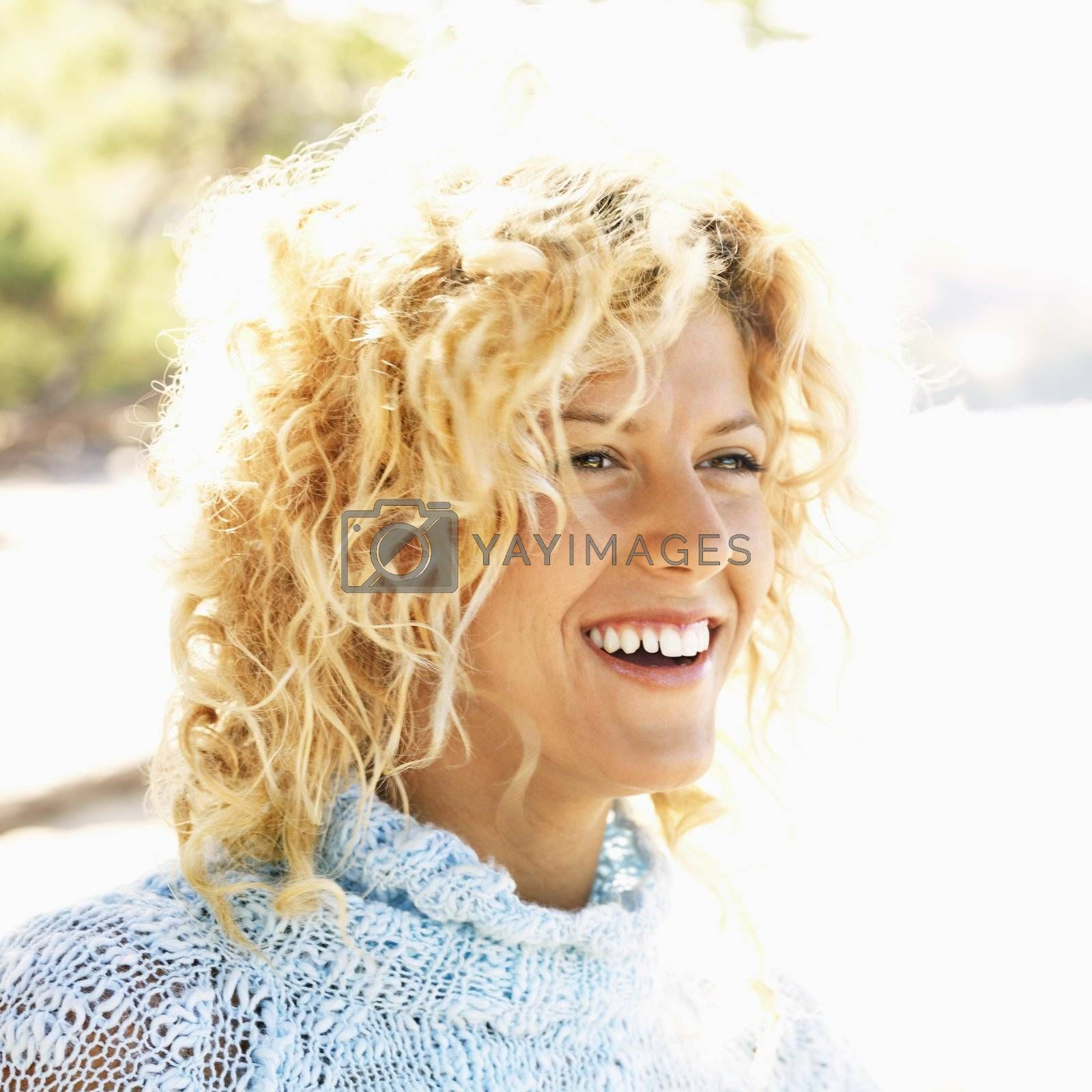 Close up portrait of attractive young blond woman smiling.