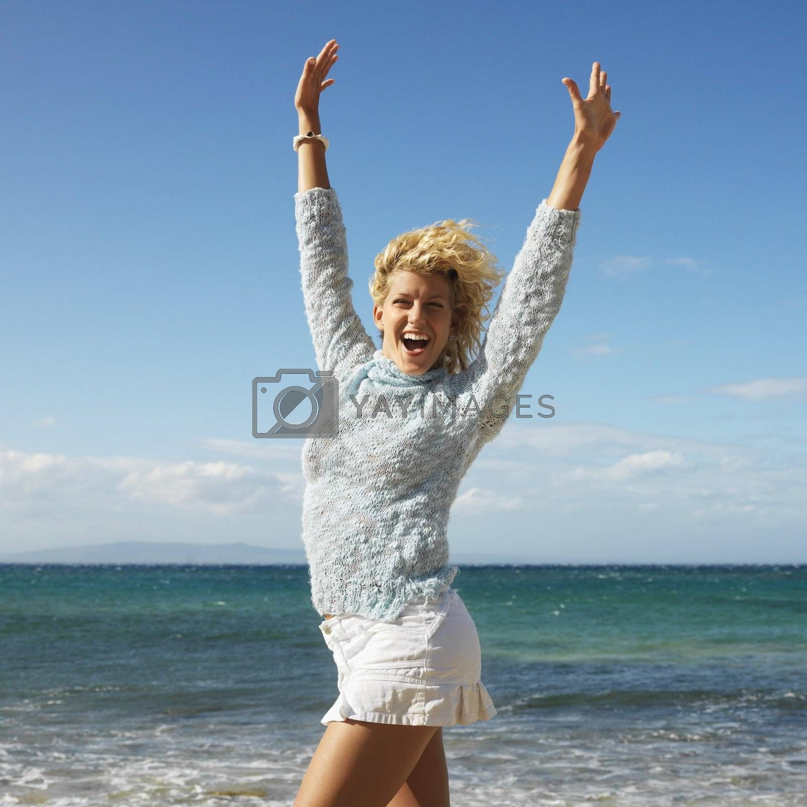 Portrait of attractive young blond woman smiling with arms raised in air on Maui, Hawaii beach.