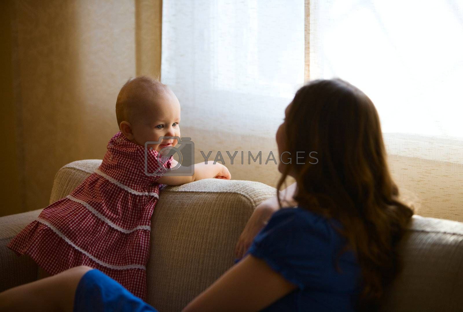 Lifestyle photo of mother and baby daughter at home. Very beautiful natural light