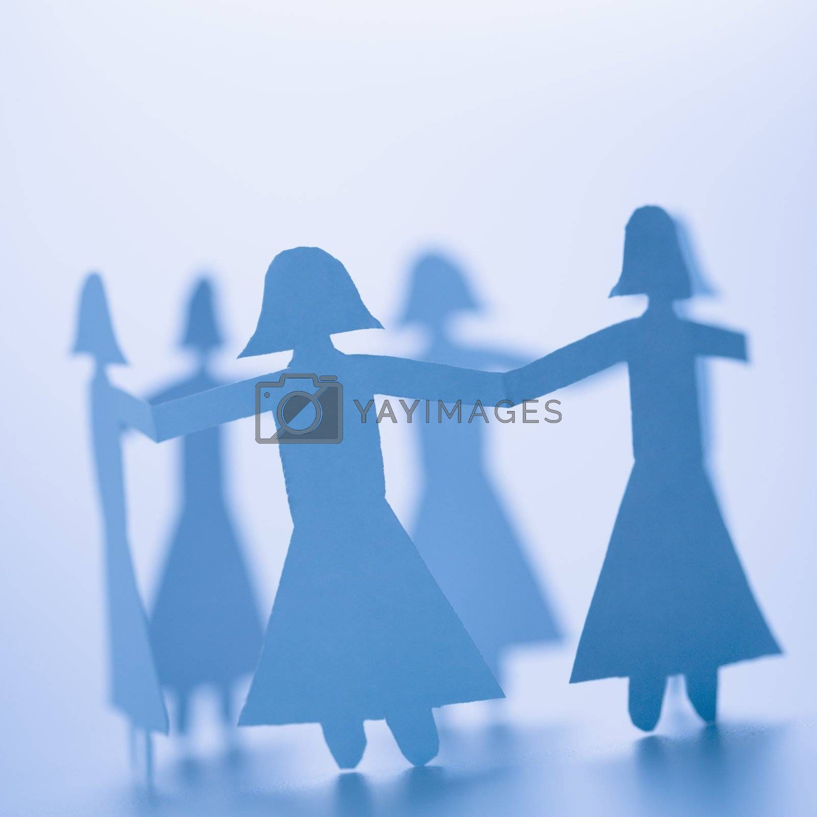 Paper cutout girls holding hands standing in circle.
