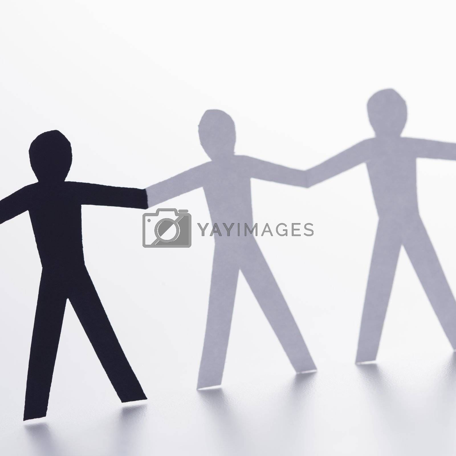 Black and white cutout paper people holding hands.