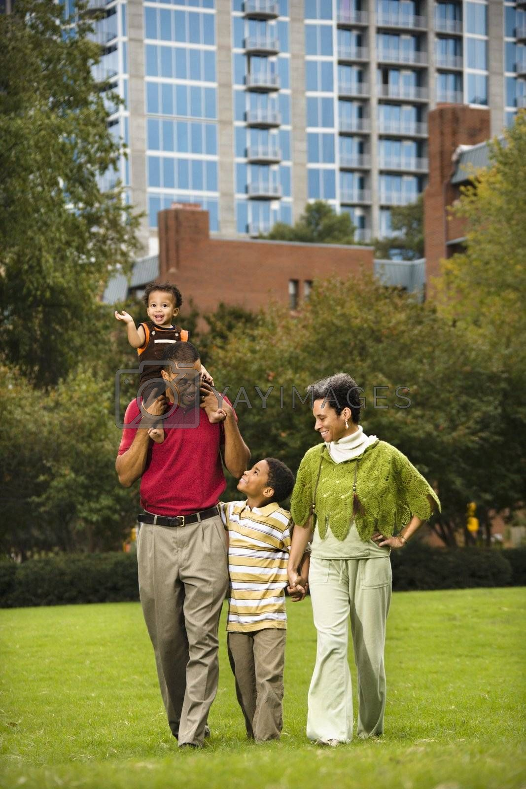 Family of four people walking in park smiling.
