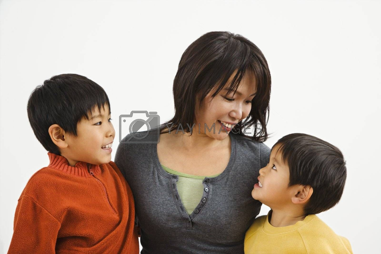 Asian mother and two sons smiling at eachother.