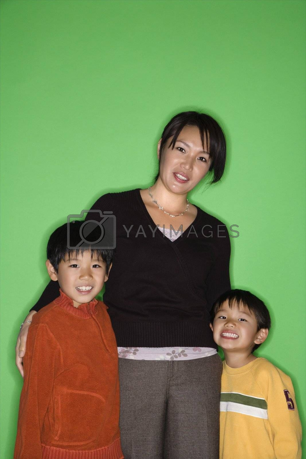 Portrait of Asian mother with two young boys smiling.