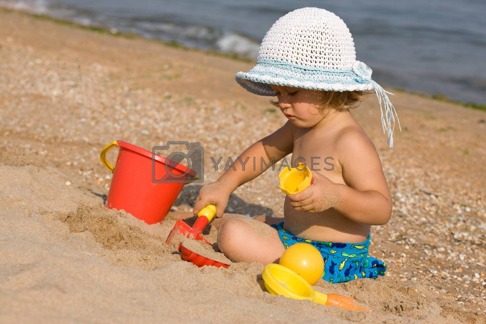 little girl in the bonnet plaing with sand,