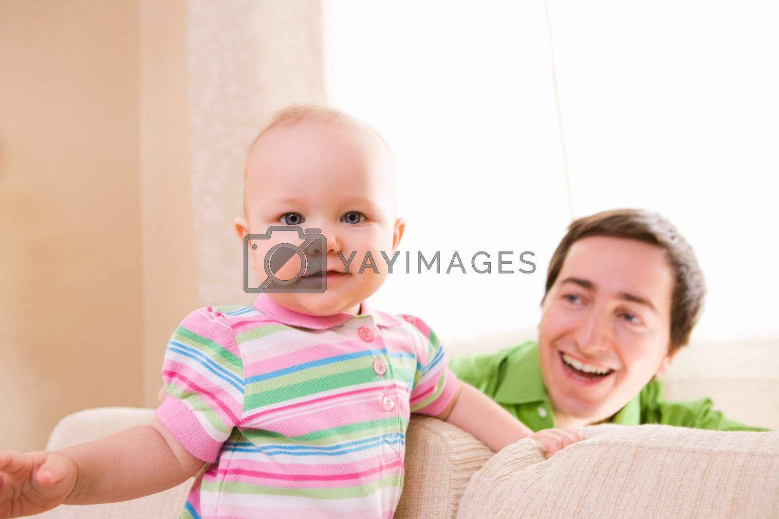 Lifestyle photo of father and baby daughter at home.