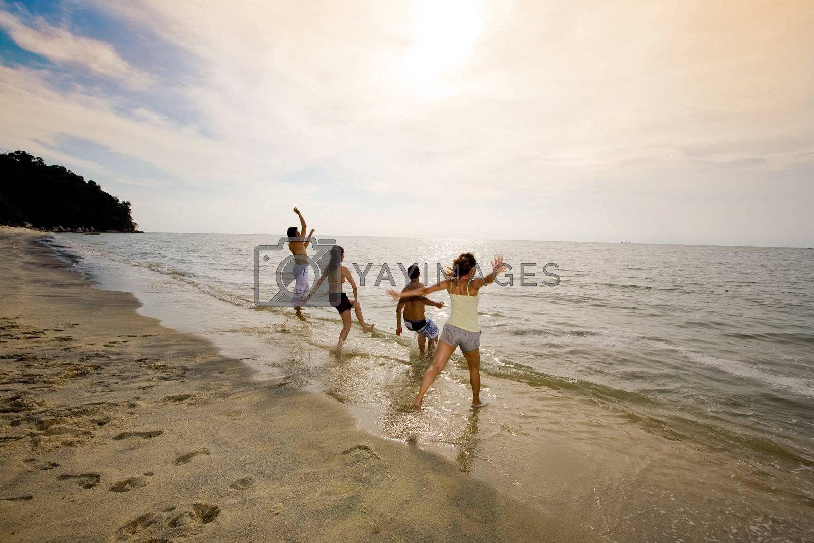 group of friends jumping at the sunset beach by eyedear