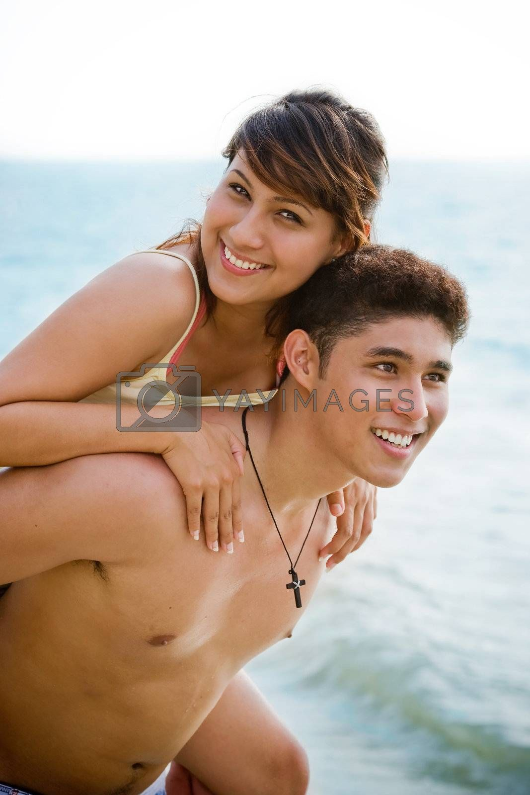 couple piggyback carrying by the beach having fun