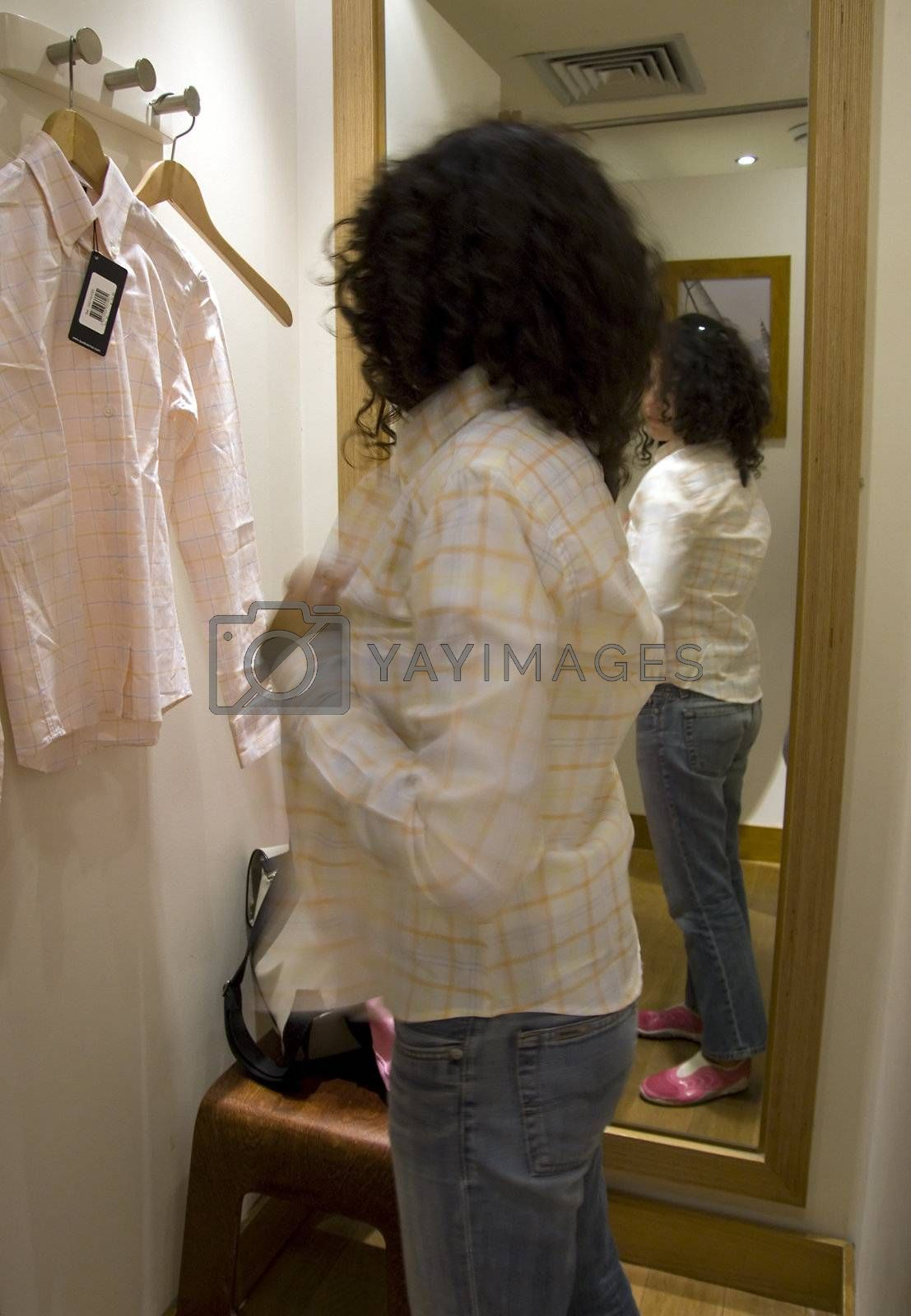 Young woman shopping ant trying a shirt by PauloResende