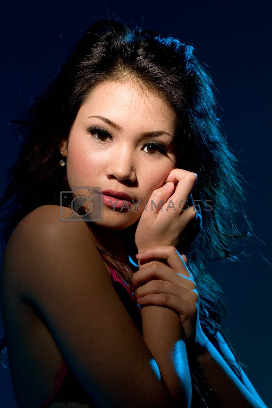 young woman with a moody sensual alluring look under blue lighting