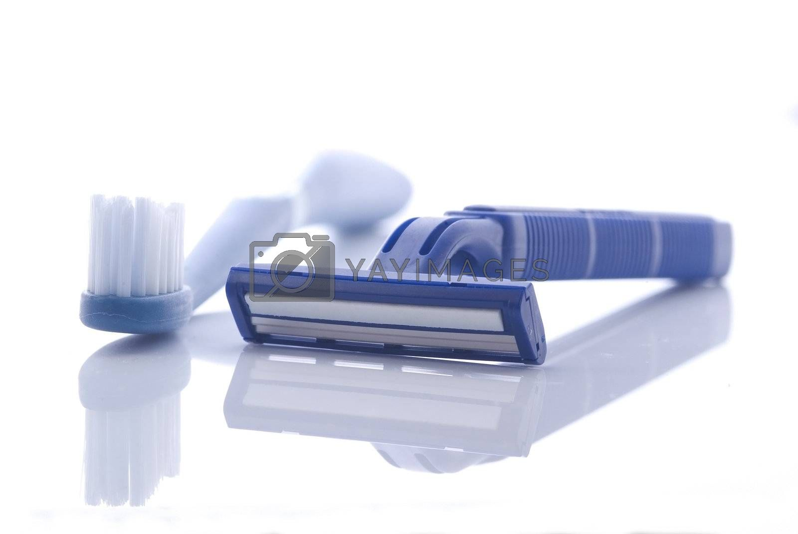 Razor and toothbrush on white by epixx