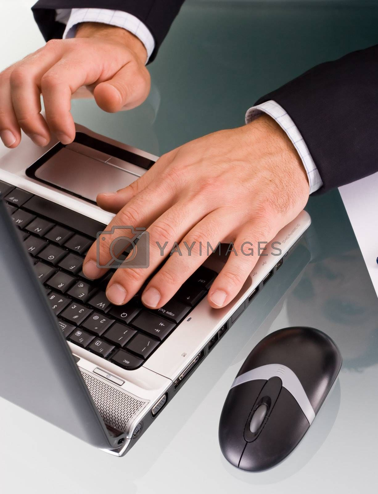 Male hands typing on a laptop computer.