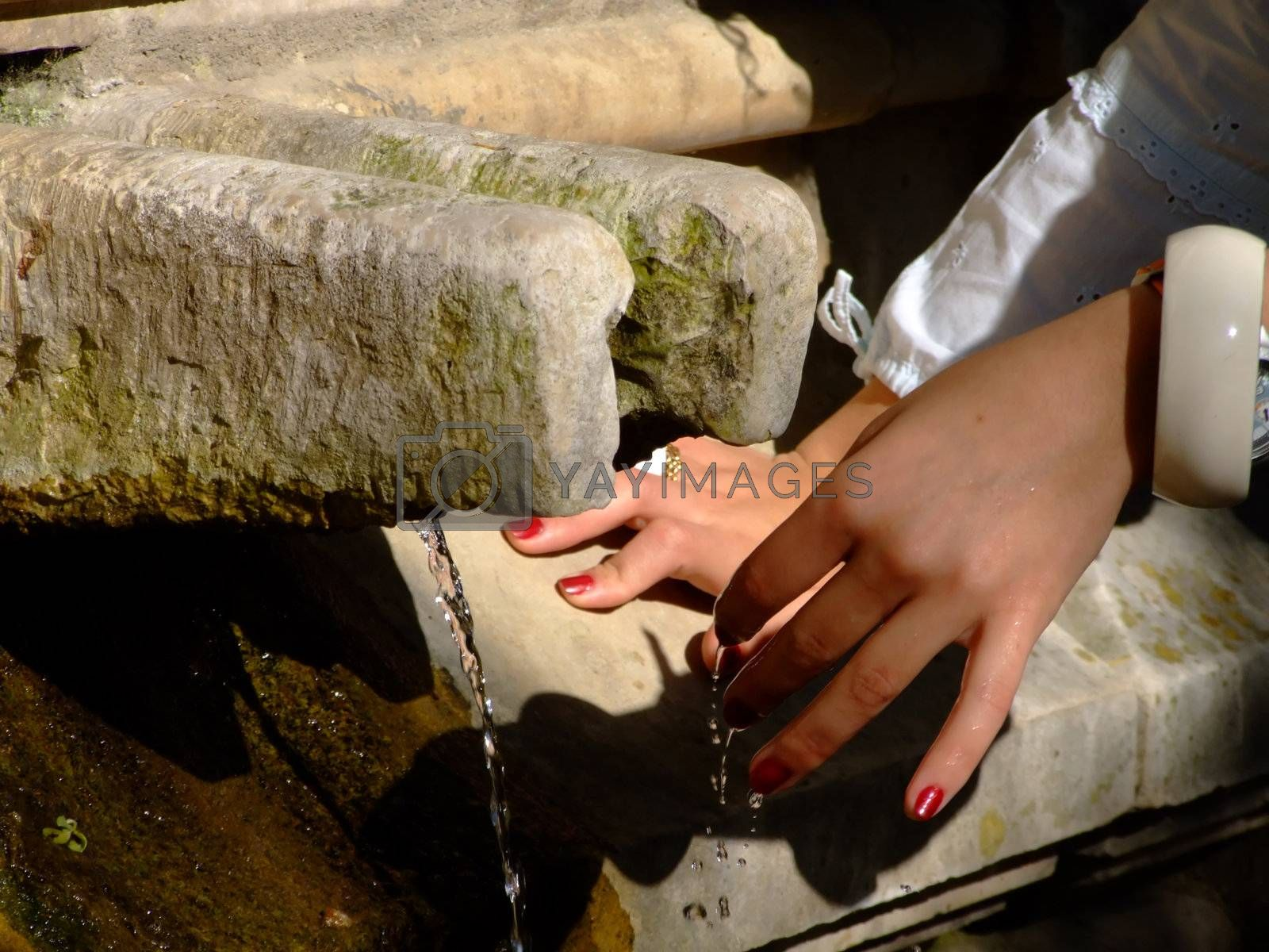 Close up on a fountain and woman hands
