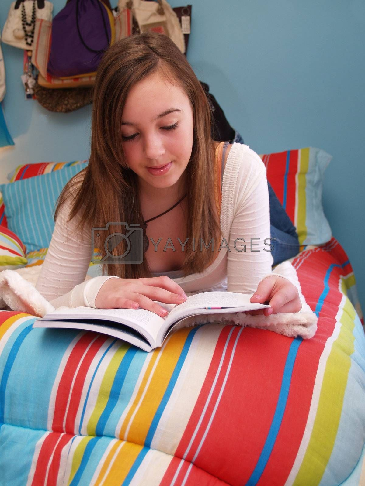 teenage girl sitting on a bed, reading a book