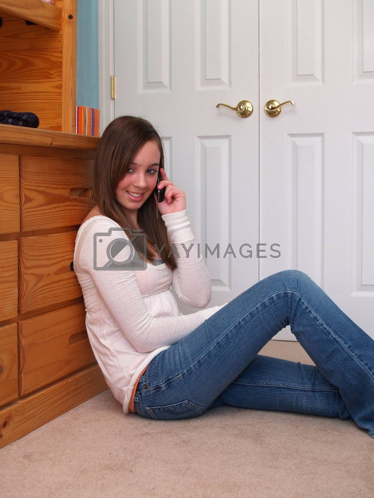 teenage girl, sitting on the floor and talking on a cell phone