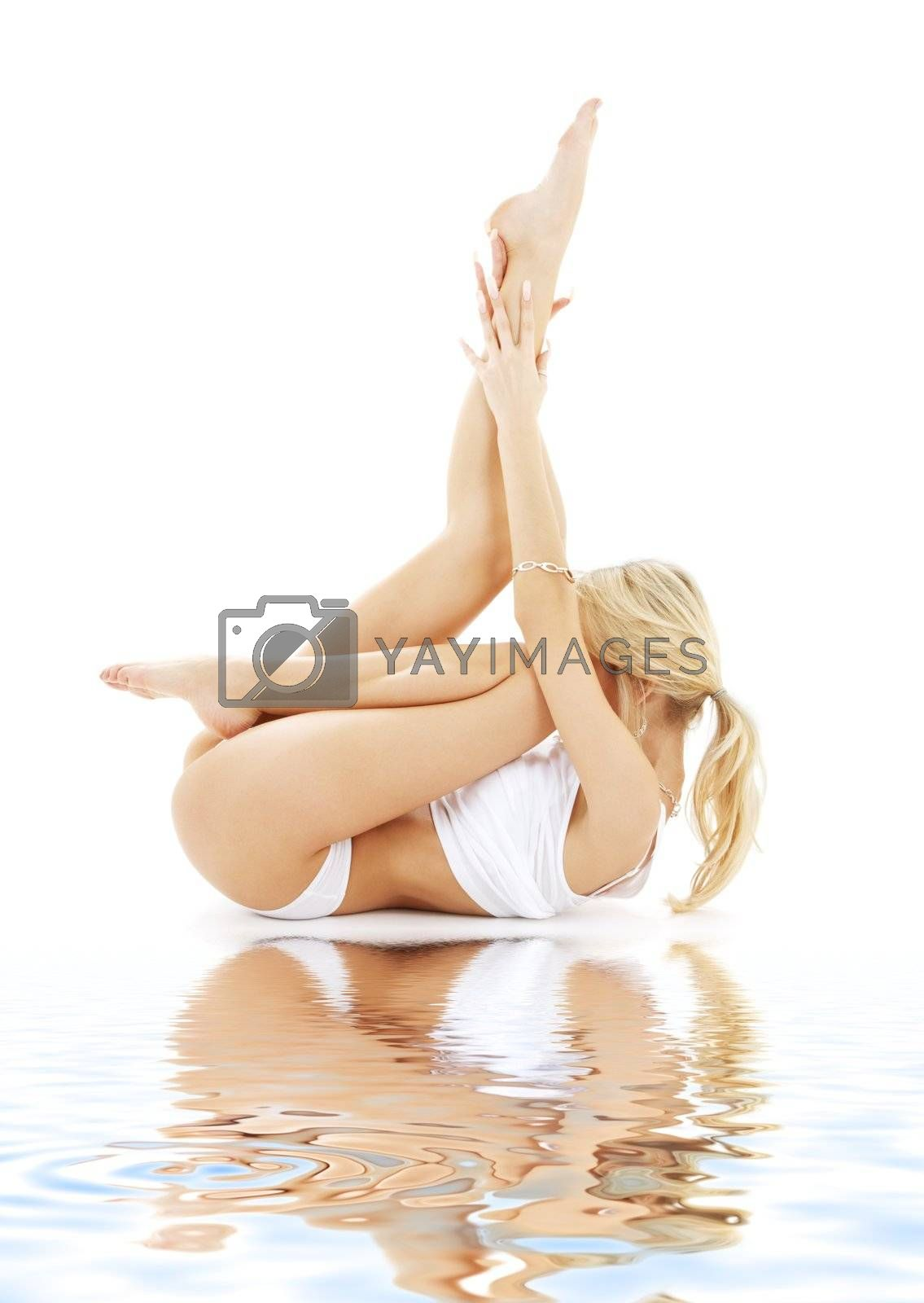 fit blond in white underwear practicing yoga on white sand