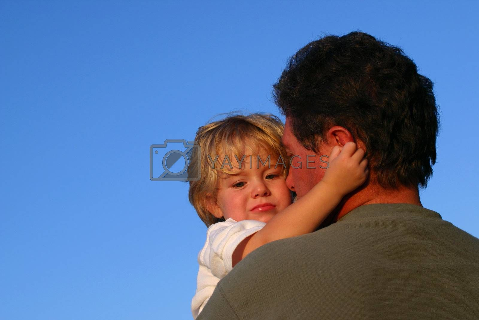 A father holds his young son will giving his a hug