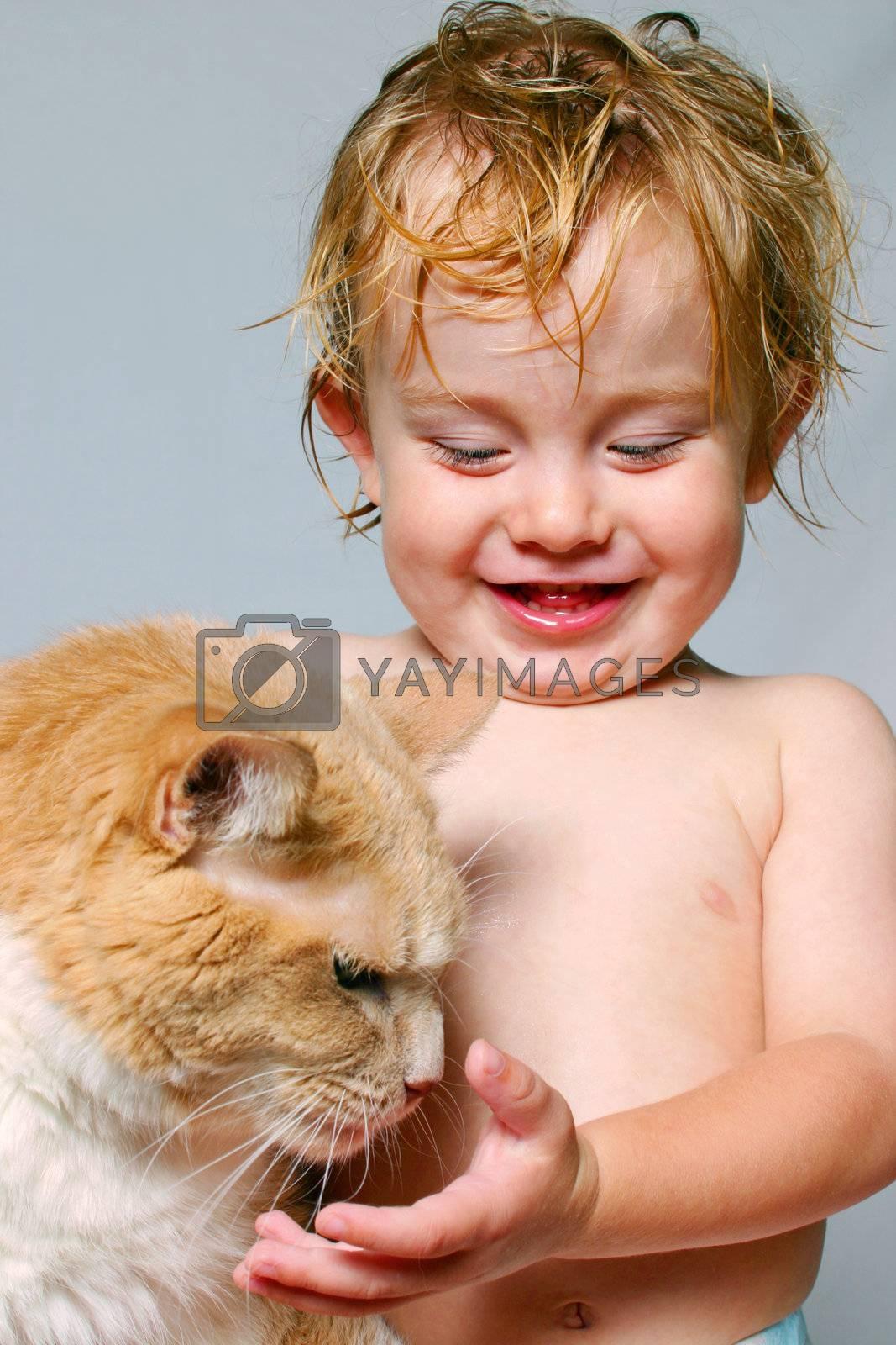 a happy young boy pets a pat