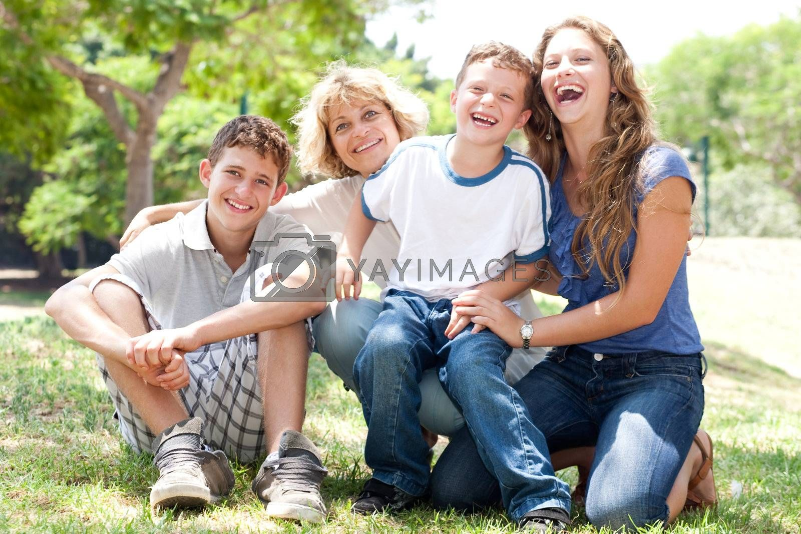 front view of happy family sitting in park and posing for camera