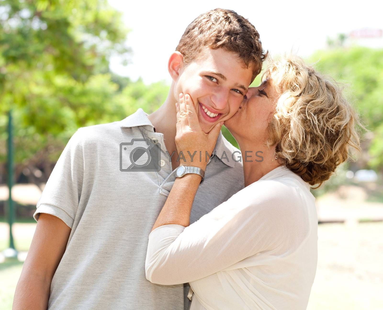 Portrait of a happy old woman kissing her adorable grandson