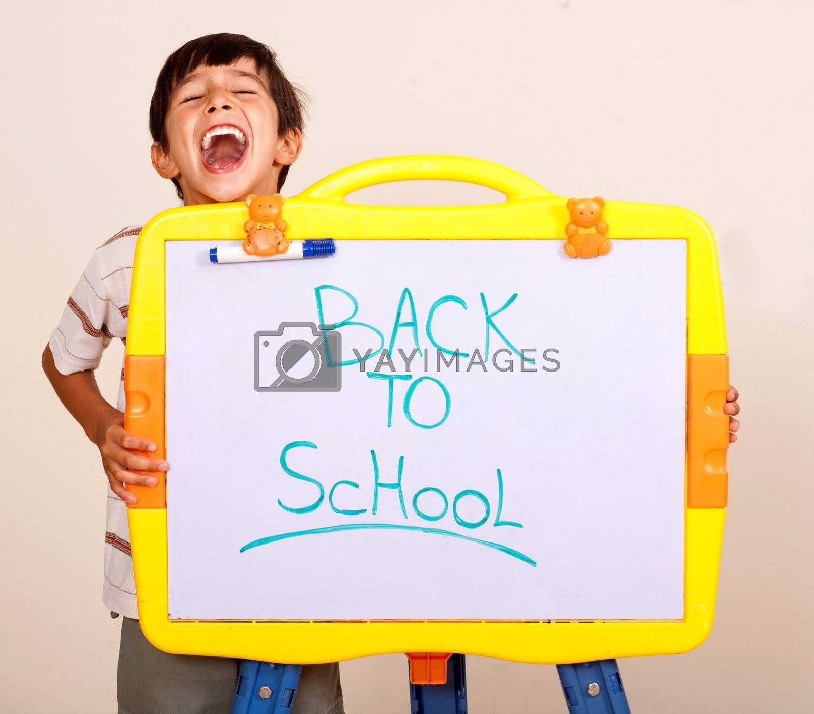 Little boy screaming with a whitebaord with text back to school on it