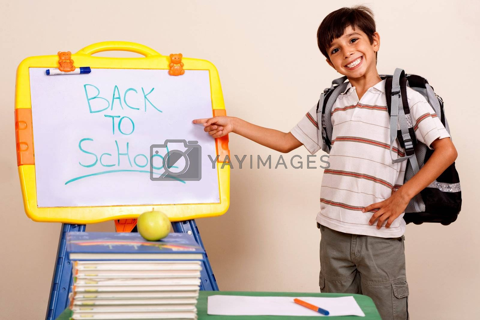 Smiling school boy pointing at white board on his classroom